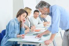 Giovani che scrivono nell'aula Immagine Stock