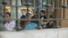 Giovani che si rilassano in caffè all'aperto archivi video