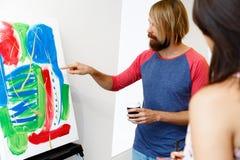 Giovani che stanno in una galleria e che contemplano materiale illustrativo fotografie stock libere da diritti
