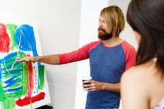 Giovani che stanno in una galleria e che contemplano materiale illustrativo fotografia stock
