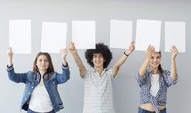 Giovani che tengono le insegne Immagini Stock Libere da Diritti