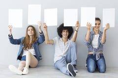 Giovani che tengono le insegne Immagine Stock Libera da Diritti