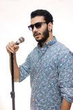 Giovani che tengono Mic Wearing Glasses And Singing una canzone Immagini Stock