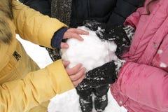 Giovani che tengono una palla di neve in sue mani nel parco di inverno fotografie stock