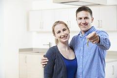 Giovani chiavi felici della tenuta delle coppie alla nuova casa fotografie stock libere da diritti