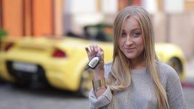 Giovani chiavi sorridenti della tenuta della donna alla nuova automobile stock footage