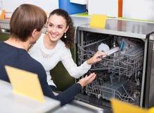 Giovani clienti che scelgono la nuova lavatrice del piatto in apparecchio Fotografia Stock