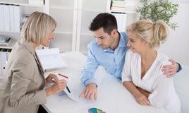 Giovani clienti delle coppie e consulente o agente che parlano del financ Immagini Stock