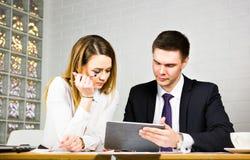 Giovani colleghi di affari che discutono lavoro su un computer portatile nello spazio dilavoro, persone di affari corporative Immagine Stock