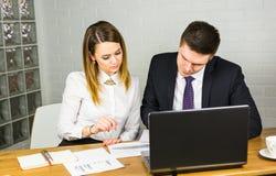 Giovani colleghi di affari che discutono lavoro su un computer portatile nello spazio dilavoro, persone di affari corporative Fotografia Stock