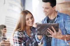 Giovani colleghi positivi che per mezzo della compressa Immagini Stock Libere da Diritti