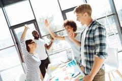 Giovani colleghi positivi che ritengono felici dopo il loro riuscito progetto Immagini Stock