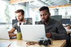 Giovani colleghi seri che si siedono nell'ufficio che coworking Immagini Stock