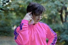 Giovani colloqui caucasici bei dell'uomo sul telefono cellulare che sta nel parco Vetri dorati rotondi, camicia lilla luminosa, g immagini stock libere da diritti