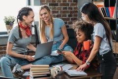 Giovani compagni di classe sorridenti che studiano insieme ai libri ed ai dispositivi digitali Immagini Stock