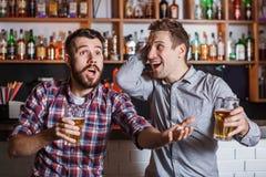 Giovani con calcio di sorveglianza della birra in una barra Fotografie Stock