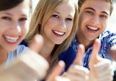 Giovani con i pollici in su Fotografie Stock