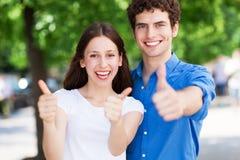 Giovani con i pollici su Fotografia Stock