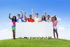 Giovani con il cartello Fotografia Stock