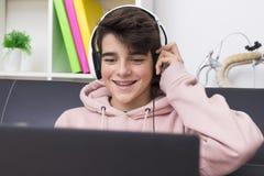 Giovani con il computer e le cuffie Fotografia Stock