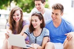 Giovani con il computer portatile all'aperto Fotografie Stock