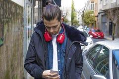 Giovani con il telefono cellulare sulla via fotografia stock