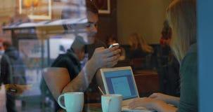 Giovani con lo Smart Phone ed il computer portatile in caffè video d archivio