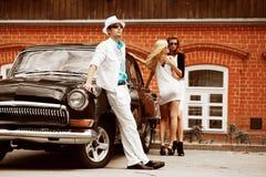 Giovani con una retro automobile Fotografie Stock Libere da Diritti