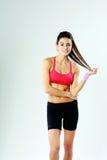Giovani condizione e tenuta sorridenti della donna di sport i suoi capelli Immagini Stock