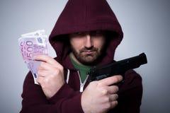 Giovani contanti e pistola incappucciati della tenuta dell'uomo in sue mani Fotografia Stock Libera da Diritti