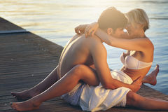 Giovani coppie abbracciate sul pilastro del mare immagine stock libera da diritti