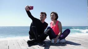 Giovani coppie adatte che si siedono vicino al telefono della tenuta della spiaggia e che prendono posa dei selfies Ragazzo felic video d archivio