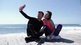Giovani coppie adatte che si siedono vicino al telefono della tenuta della spiaggia e che prendono posa dei selfies Ragazzo felic archivi video