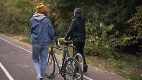 Giovani coppie adorabili che abbracciano iniziare a camminare con le bici nel parco della città nel parco di autunno Concetto del video d archivio