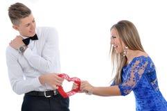 Giovani coppie adorabili che tengono insieme cuore rosso Immagini Stock
