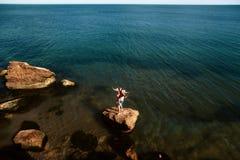 Giovani coppie adulte adorabili sulle rocce nel mare vicino alla spiaggia con le grandi scogliere, Mar Nero, Odessa, Ucraina, pos fotografie stock