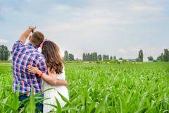 Giovani coppie adulte amorose felici che spendono tempo sul campo il giorno soleggiato Immagine Stock