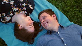 Giovani coppie adulte felici che si trovano sull'erba sopra il tramonto Ragazza attraente vicino al tipo bello archivi video