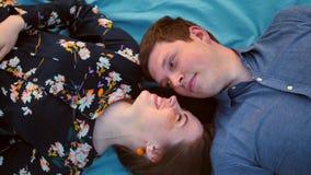 Giovani coppie adulte felici che si trovano sull'erba sopra il tramonto Sorridere e ridere archivi video