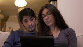 Giovani coppie affettuose che si siedono sullo strato nella vita, stanza con il pc della compressa che passa in rassegna Internet archivi video