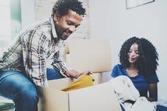 Giovani coppie africane americane nere con le scatole commoventi in nuovo appartamento Coppie allegre che si siedono nella nuova  Immagini Stock