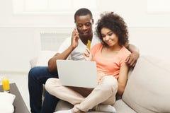 Giovani coppie afroamericane che lavorano al computer portatile, spazio della copia immagini stock