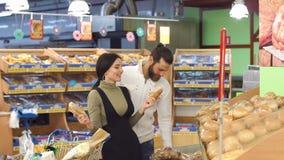 Giovani coppie alla moda che comprano pane fresco in un supermercato video d archivio