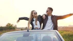 Giovani coppie alla moda che godono di bello paesaggio durante il resto dopo il viaggio nel cabriolet stock footage