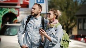 Giovani coppie alla moda che stanno sullo smartphone del centro urbano e di uso L'uomo e la donna esaminano la mappa per trovare  stock footage