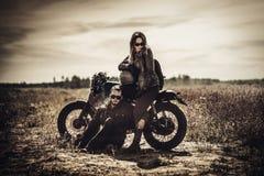 Giovani, coppie alla moda del corridore del caffè sui motocicli su ordinazione d'annata nel campo immagine stock