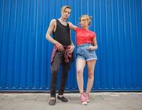 Giovani coppie alla moda moderne su fondo blu, adolescenti soleggiati dei pantaloni a vita bassa delle coppie del ritratto fotografia stock libera da diritti
