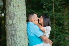 Giovani coppie alla moda nell'amore e baciare fuori dall'albero immagini stock