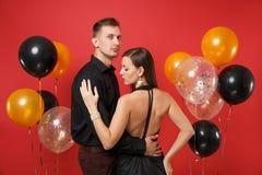 Giovani coppie alla moda in vestiti neri che celebrano il partito di festa di compleanno sull'aria rossa luminosa del fondo immagine stock
