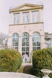 Giovani coppie alla moda vicino alla vecchia casa beige con le colonne e le grandi finestre d'annata Nozze romantiche a Parigi immagini stock libere da diritti
